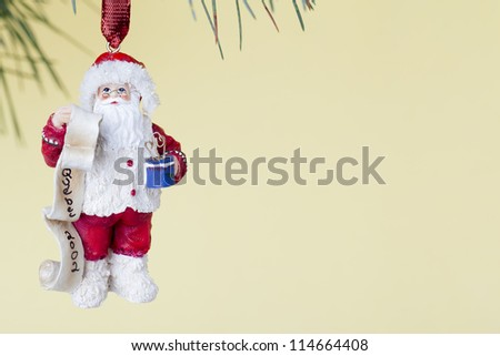 Santa Christmas bauble hanging on Christmas tree against yellow background.