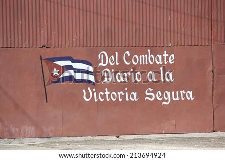Santa Clara, Cuba, August 20, 2012: Cuba's politic propaganda, revolutionary slogan. A wall script in favour of the revolution, from combat to victory - stock photo