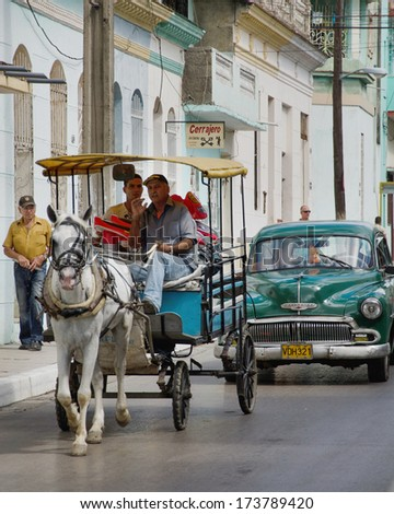 SANTA CLARA, CUBA- JANUARY 8, 2013: The Communist government has introduced changes to its economic structure allowing private transportation. People profit from it using old cars and different means. - stock photo