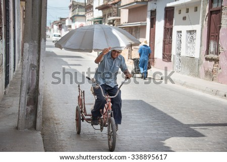 SANTA CLARA,CUBA-JULY 5,2015:Senior riding a bicycle and protecting against the intense sun with a large or beach umbrella. Cuba has registered higher than average temperatures in the latest years.