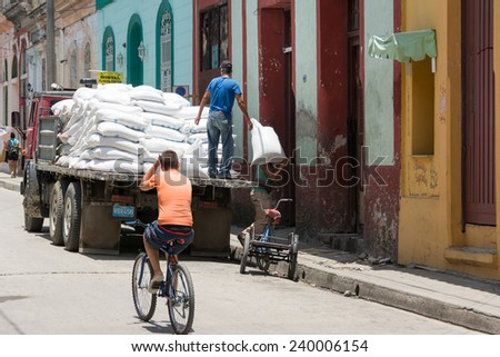SANTA CLARA,CUBA-JULY 4,2014: Unloading a truck of flour in a Cuban dining room for people in need or social cases. One of the major achievements of the Cuban Revolution is serve those in need.