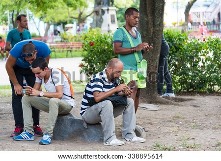 SANTA CLARA,CUBA-JULY 5,2015:Wifi internet in main city plazas.Cubans brave obstacles to connect to internet: some read emails and browse but most of them use applications to talk with family abroad. - stock photo