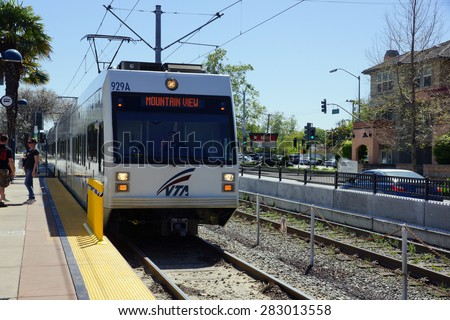 SANTA CLARA - MARCH 29: People stand as VTA train transit lightrail arrives into station 'Mountain View' bound in San Jose, California on March 29, 2015. - stock photo