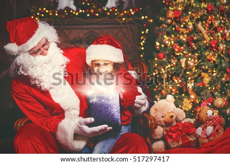 Santa Claus and child girl with bright magical gift in Christmas night
