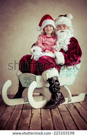 Santa Claus and child riding on sleigh. Christmas concept. Family holiday - stock photo