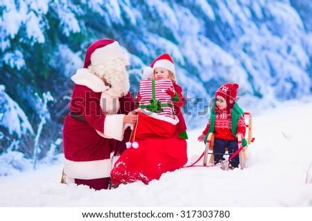Santa Claus and children opening presents in snowy forest. Kids and father in Santa costume and beard open Christmas gifts. Little girl helping with present sack. Xmas, snow and winter fun for family - stock photo
