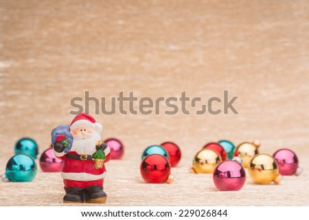 Santa Claus and christmas balls on illuminated background - stock photo