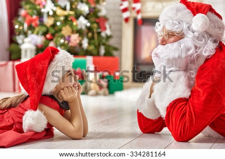 Santa Claus and cute girl getting ready for Christmas. - stock photo