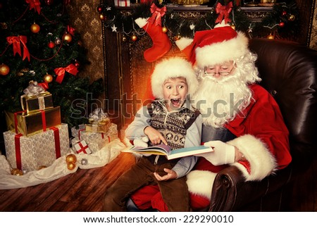 Santa Claus and happy boy sitting in Christmas room and reading a book. Christmas home d�©cor.  - stock photo