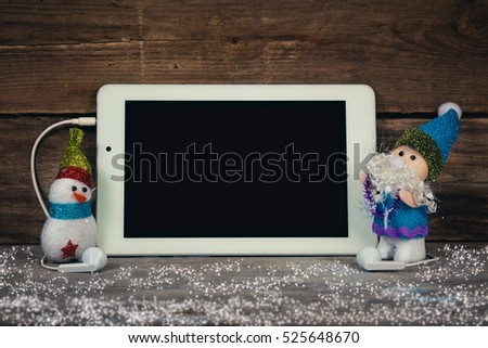Santa Claus and snowman holding tablet.