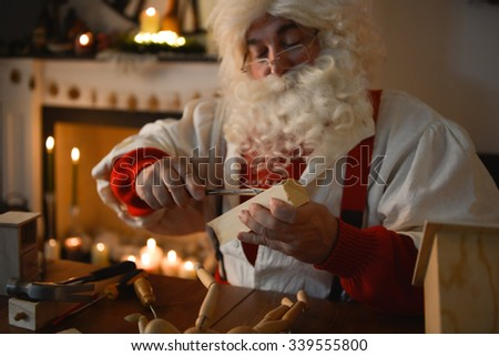Santa Claus at Home carving something from wooden plank