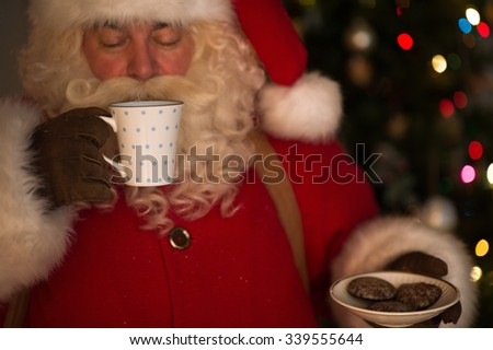 Santa Claus at Home eating cookies and drinking milk - stock photo
