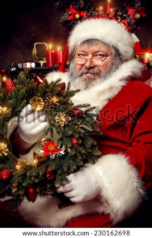 Santa Claus at home making gifts for Christmas. Decoration. - stock photo