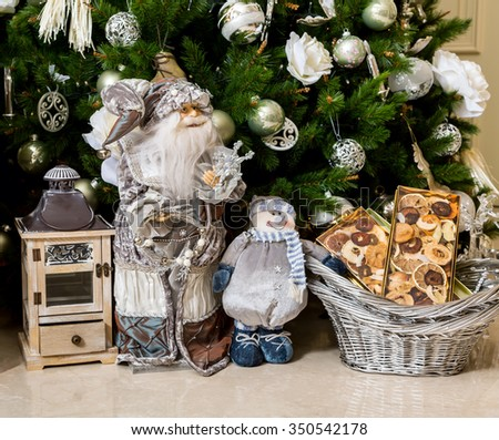 Santa Claus, basket with mandarins and lantern-candlestick with gifts in New Year's holiday under Christmas tree - stock photo