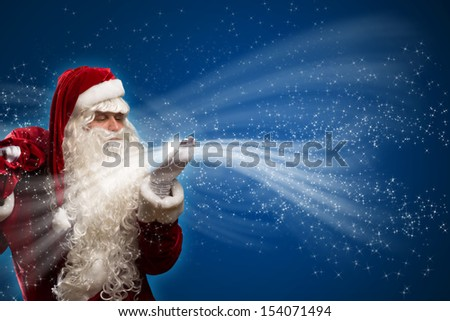 santa claus blows with hands magic sparks holds on shoulder bag with Christmas presents