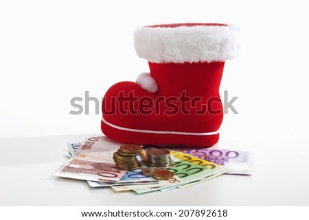 Santa Claus boot and euro coins on fanned euro notes against white background - stock photo