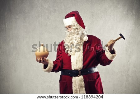 Santa Claus breaking a vessel of money with a hammer - stock photo
