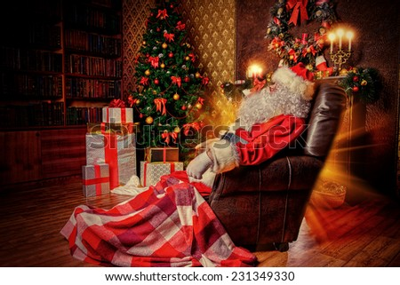 Santa Claus brought gifts for Christmas and having a rest by the fireplace. Home decoration. - stock photo
