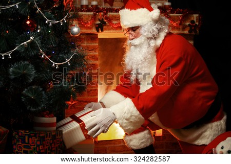 Santa Claus brought gifts for Christmas and having a rest by the fireplace. Home decoration.
