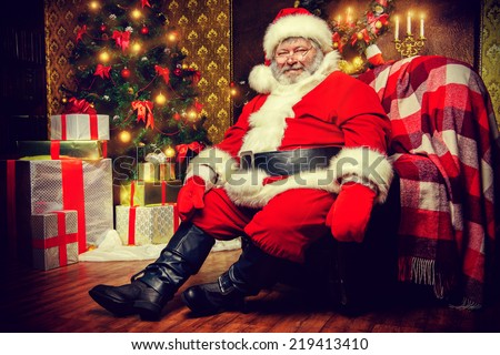 Santa Claus brought gifts for Christmas and sat down to rest by the fireplace. Home decoration. - stock photo