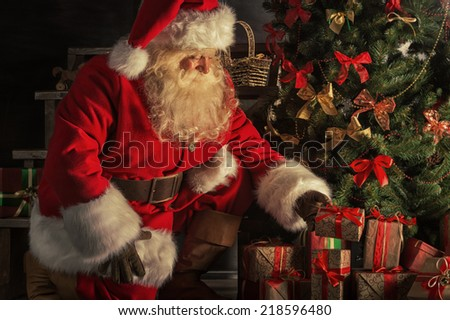Santa Claus brought gifts for Christmas. Santa is placing gift boxes under Christmas tree - stock photo