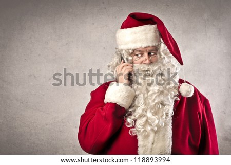 Santa Claus calling with a mobile phone - stock photo