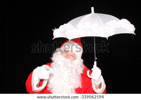 Santa Claus carries an umbrella while checking to see if its going to snow. Santa Claus weather. Christmas Snow. Snow for Christmas. Christmas Eve. Santa loves snow.  - stock photo
