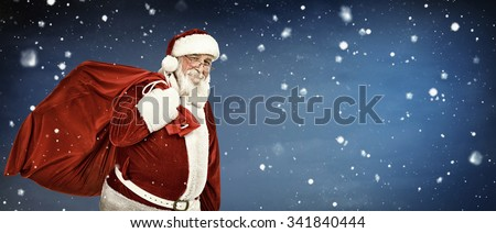 Santa Claus carrying  a bag full of gifts, on copyspace background - stock photo