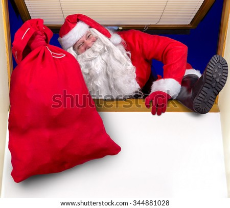 Santa Claus carrying a bag of gifts and climbs into the room through the window - stock photo