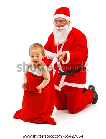 Santa Claus carrying a little boy in his bag - stock photo
