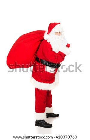 Santa Claus carrying bag with presents - stock photo