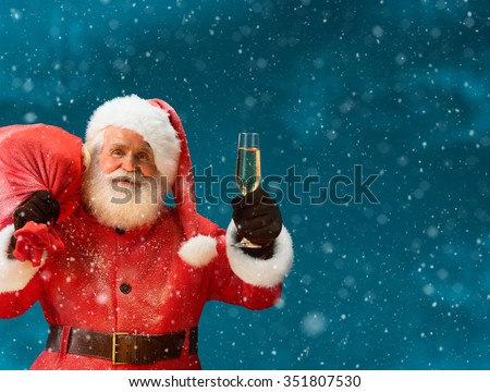 Santa Claus carrying big bag full of gifts with a glass of champagne and looking at camera / Merry Christmas & New Year's Eve concept / Closeup on blurred blue background. - stock photo