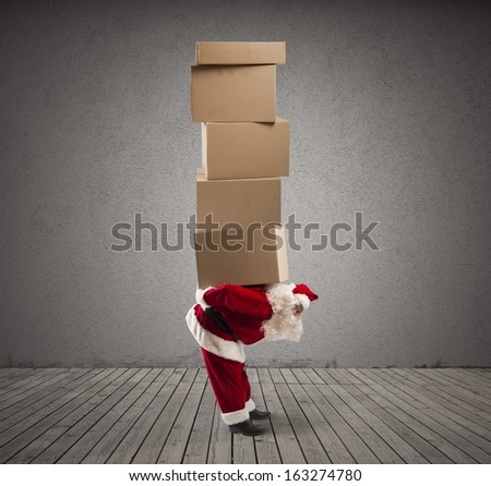 Santa Claus carrying on his back many gifts - stock photo