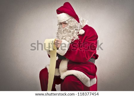 Santa Claus checking out the gift list - stock photo