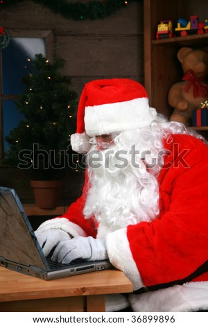 Santa Claus checks his e-mail on his laptop computer - stock photo
