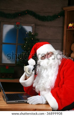 Santa Claus checks his e-mail on his laptop computer