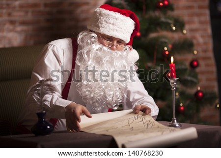 Santa Claus checks his list on the background of the Christmas tree - stock photo