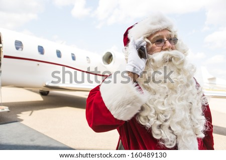 Santa Claus communicating on mobile phone against private jet at airport terminal - stock photo