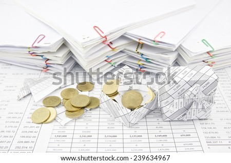 Santa Claus discover gold coin in gift box on finance account with pile of paperwork as background.