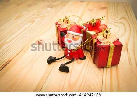 Santa Claus doll against gift box with ball on wood background - stock photo