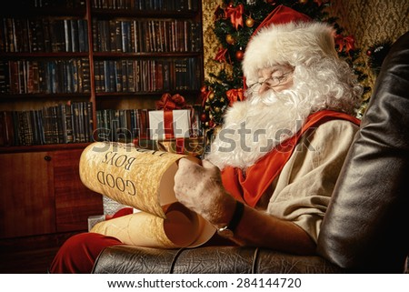Santa Claus dressed in his home clothes sitting in the room by the fireplace and Christmas tree. He is reading a list of good boys and girls. Christmas. Decoration. - stock photo