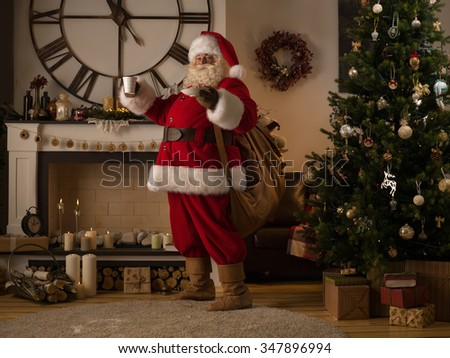 Santa Claus Drinking Milk near Fireplace at Home - stock photo