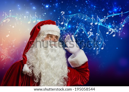 Santa Claus enjoying the sound of music - stock photo