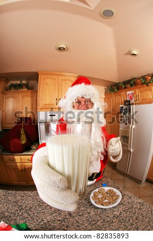 Santa Claus enjoys cookies and milk in a kitchen on fine christmas eve - stock photo