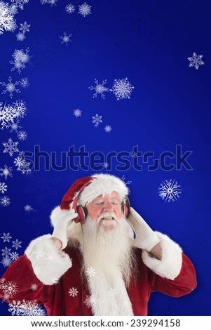 Santa Claus enjoys some music against blue - stock photo