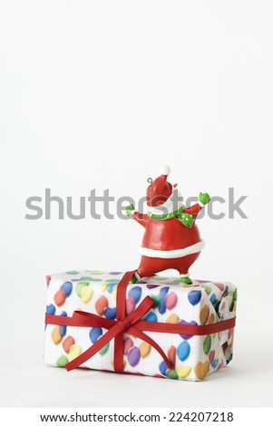 Santa Claus figurine standing on top of Christmas present, rear view - stock photo