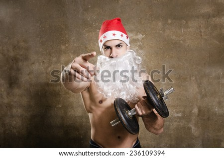 Santa Claus fitness guy pointing you for training after Christmas - stock photo
