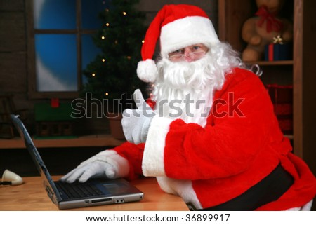 "Santa Claus flashes the ""thumbs up"" sign checking his e mail"