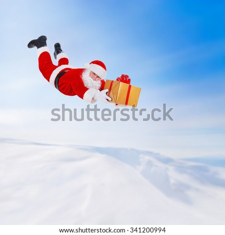 Santa Claus flying fall over with big golden gift box above snowy winter landscape, Happy New Year and Merry Christmas coming concept