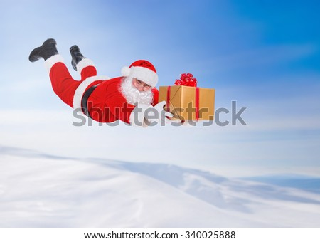 Santa Claus flying fall over with big golden gift box above snowy winter landscape, New Year's Day or X-mas Happy New Year and Merry Christmas concept